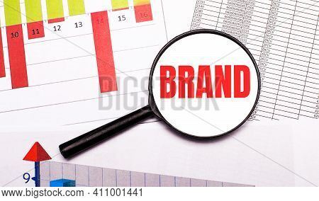 N The Desktop, Graphs, Reports, A Magnifying Glass With The Inscription Brand. Business Concept
