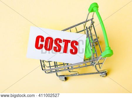 The Card With The Word Costs Is In The Shopping Cart. Marketing Concept