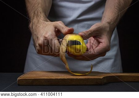Potatoes On A Dark Background. The Cook Peels The Potatoes With A Knife. Male Hands Peeling Potatoes
