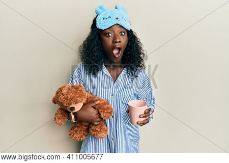 Beautiful african young woman wearing pajama, holding teddy bear and drinking coffee afraid and shocked with surprise and amazed expression, fear and excited face.