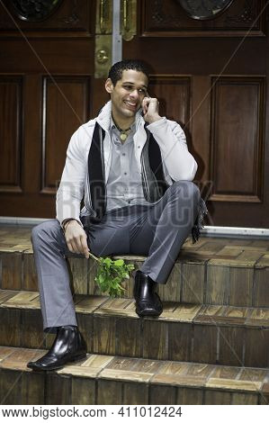 Holding Small Green Plants And Talking On The Phone, A Young Guy Is Sitting On Door Steps And Waitin