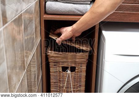 A Person Opens A Lid Of A Wicker Laundry Basket Near A Modern Washing Machine In A Laundry Room. Sca