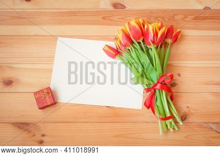 Bouquet Of Fresh Tulips With Red Ribbon, Empty Card For Your Text And Red Gift Box On Wooden Backgro