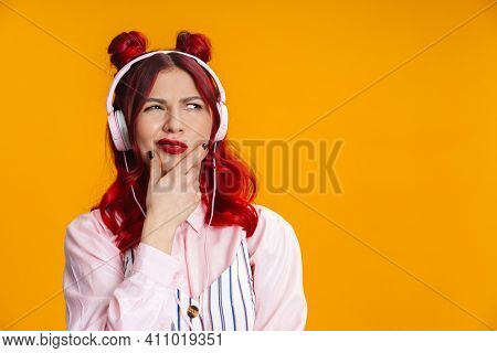 Displeased redhaired girl in headphones looking aside isolated over yellow background