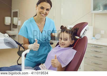 Woman Dentist And Girl Patient Showing Thumbs Up Sign And Smiling During Teeth Examination In Dentis