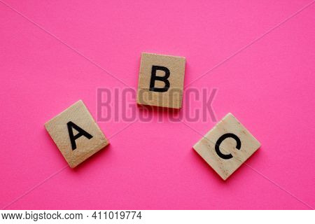 Abc Is Alphabetical Characters On A Pink Background. Wooden Alphabetical Blocks, Isolated Against A
