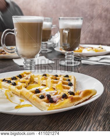 Homemade Coffee With Waffles On A White Plate. Tall Transparent Glass With Beverage. Traditional Bre