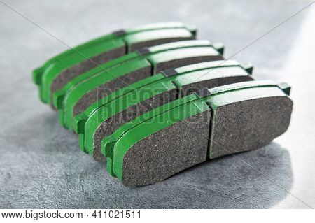 A Set Of New Green Brake Pads On A Gray Table