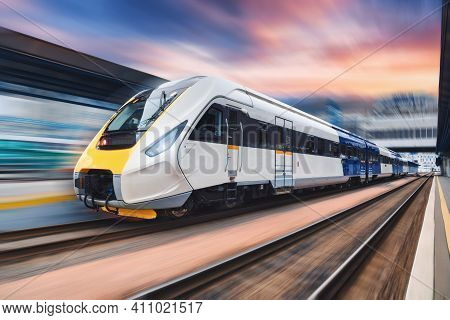 High Speed Train In Motion On The Railway Station At Sunset. Modern Intercity Passenger Train With M