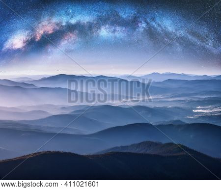 Milky Way Arch Over The Mountains In Fog At Starry Night In Summer. Landscape With Blue Sky With Sta