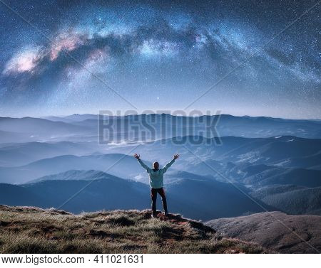 Happy Man On The Mountain Peak And Arched Milky Way Over Mountains In Low Clouds At Night. Landscape
