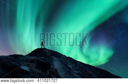 Northern Lights And Silhouette Of Standing Man With Raised Up Arms On The Mountain In Norway. Aurora