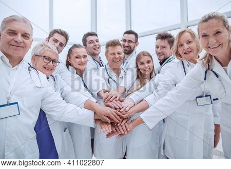 large group of doctors put their hands together.