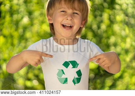 Happy Child Points Fingers At Recycle Sign On T-shirt. Funny Kid Against Spring Green Background. Ec