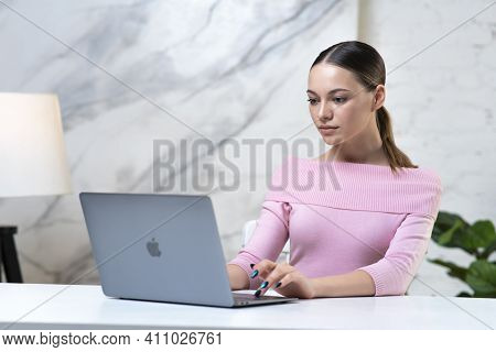 Saint-petersburg, Russia - 03.03.2021: Beautiful Girl, Young Woman Freelancer Is Working On Her Lapt