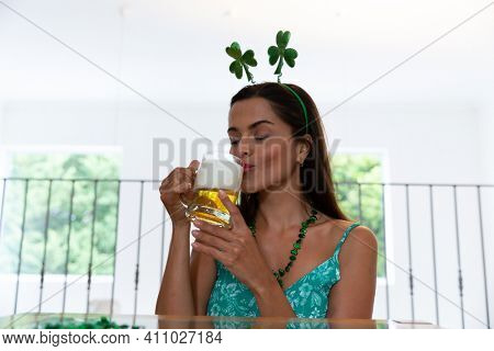 Caucasian woman celebrating st patrick's day making video call wearing deely boppers drinking beer. staying at home in isolation during quarantine lockdown.