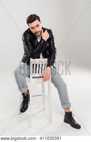 Bearded Stylish Man Sitting On Shite Chair On Grey Background