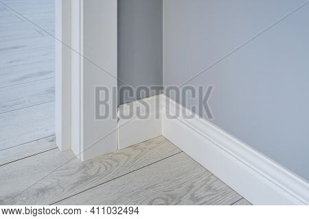 Detail Of Corner Flooring With Intricate Crown Molding And Plinth.