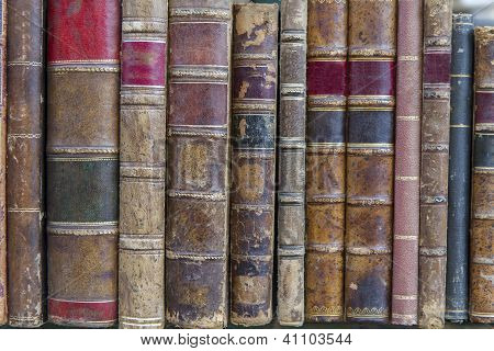 A pile of old weathered books in a shelf
