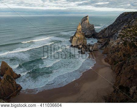Aerial Panorama Of Waves Crashing On Shore Of Praia Da Ursa Atlantic Coast Rocky Cliff Sand Beach Ca