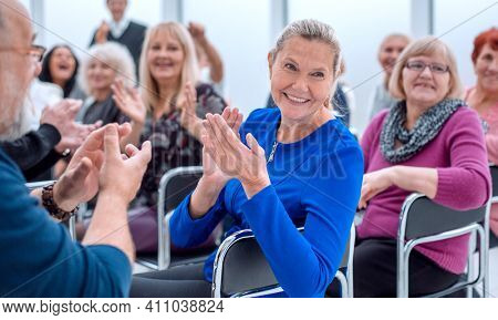 a group of elderly people are sitting in a circle clapping their