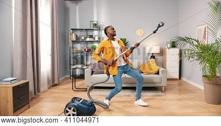 African American Joyful Happy Handsome Young Guy Vacuuming Living Room At Home Doing Housework Danci