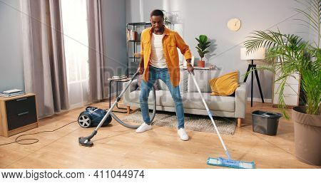 Cheerful Handsome African American Young Man In Positive Mood Cleaning House, Vacuuming And Washing