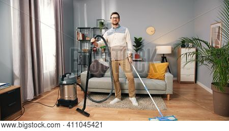 Caucasian Handsome Busy Serious Man Cleaning Living Room At Home Vacuuming And Mopping Floor At A Ti