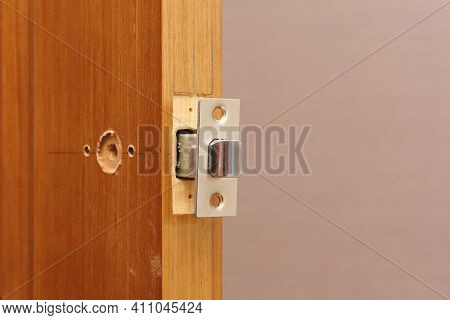 Inserting Door Latch In End Hole Close-up. Fitting Door Lock In Panel. Markup For Hole Drilling For