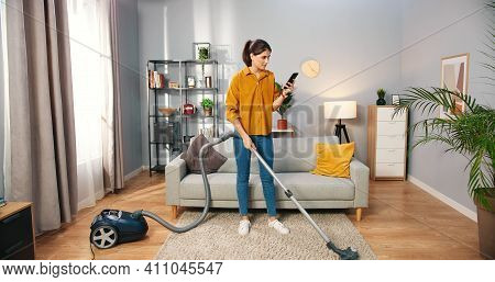 Happy Cheerful Young Caucasian Beautiful Woman Vacuuming Floor And Texting Surfing Internet Typing O