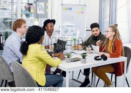 Group Of Five Multiracial Young People In Casual Outfit Sitting At Modern Office And Discussing New