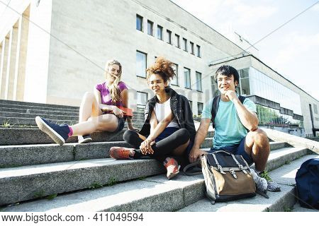 Cute Group Of Teenages At The Building Of University With Books Huggings, Diversity Nations, Having