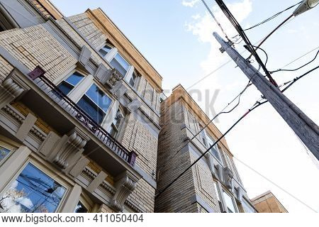 Extreme Upward View Of Old Light Brick Apartment Buildings With Power Pole And Lines, Horizontal Asp