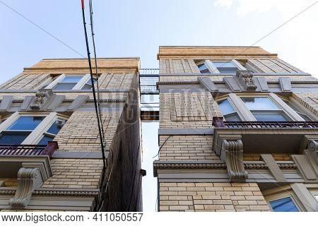 Upward View Of Space Between Two Apartment Buildings Revealing Metal Catwalks Between The Buildings,
