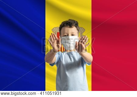 Little White Boy In A Protective Mask On The Background Of The Flag Of Andorra. Makes A Stop Sign Wi