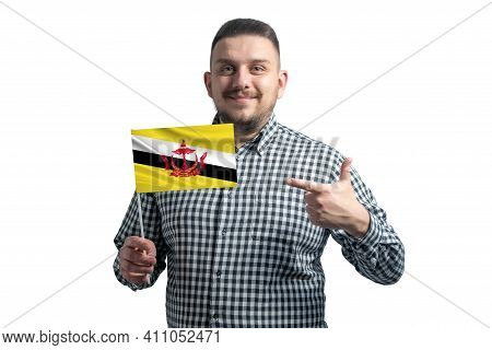 White Guy Holding A Flag Of Brunei And Points The Finger Of The Other Hand At The Flag Isolated On A