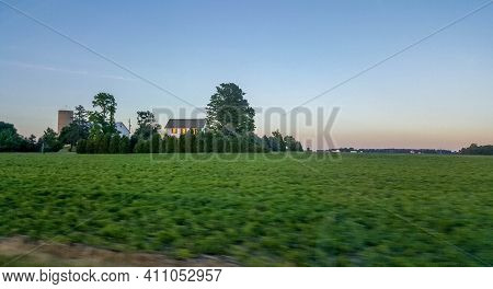 Cornfield In Summer In Motion With A Farmhouse And A Barn In The Background In The Evening Under A B