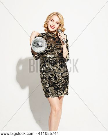 Christmas, celebration party, holiday concept. Young woman in evening dress holding microphone and disco ball. Brighrt make up and Wavy hairstyle. Party time.