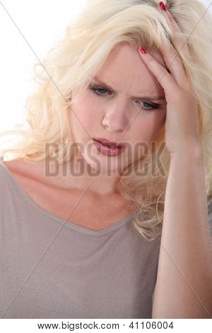 Troubled blonde woman holding her head in her hands