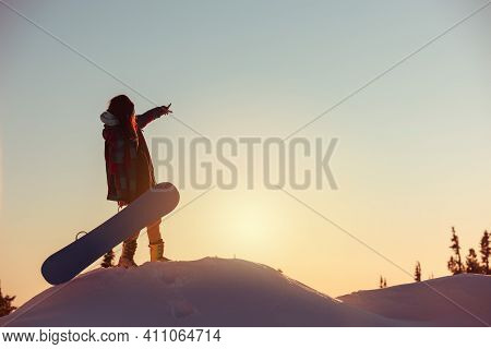 Young Girl Beginner Snowboarder Stands At Sunset Time On Mountain Top