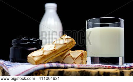 Still Life Of A Bottle Of Milk With A Glass Filled With Milk And Pastries, Jam With Milk On A Black