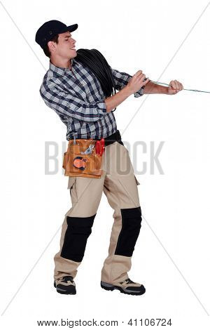 Electrician pulling on electrical cable