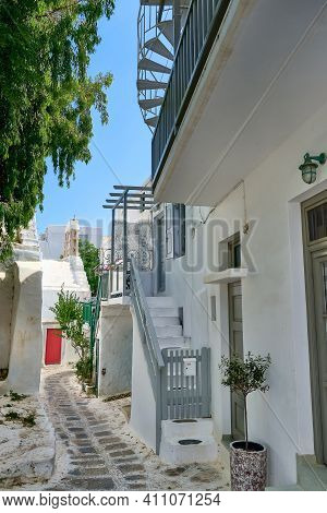 Beautiful Traditional Narrow Cobbled Streets Of Greek Island Towns. Whitewashed Houses, Flower Pots,