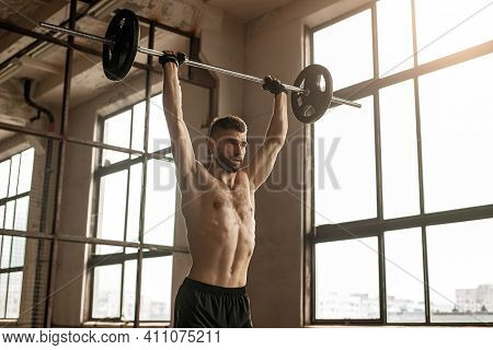 Powerful Adult Bearded Male With Naked Torso Doing Overhead Press Exercise With Barbell During Inten
