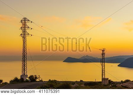 Coastline At Sunset With Electricity Transmission Pylons, Power Lines High Voltage Towers. Mesa Rold