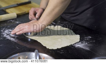 Cook Cutting Out Round Pieces Of Dough. Art. Close-up Of Professional Chef Preparing Dough For Dumpl
