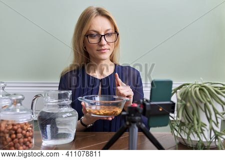 Professional Nutritionist Woman Sitting At Table With Nuts Recording Video Blog, Consulting Online U
