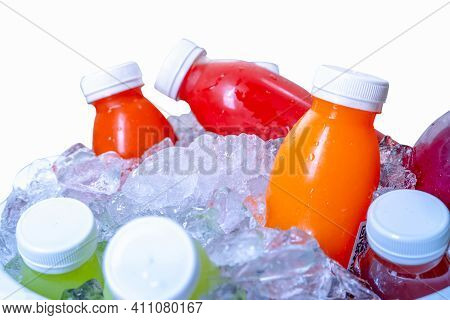 Organic Cold Pressed Raw Vegetable And Fruit Juice Bottle In Crushed Ice Bucket On White Background.