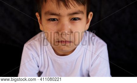 Tears In The Eyes Of A Child. The Boy Is Crying And A Tear Runs Down His Cheek. Close-up