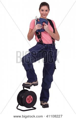 Tradeswoman holding a jigsaw with her foot propped on an extension reel